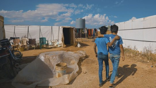 Syrian friends walking through refugee settlement in Lebanon