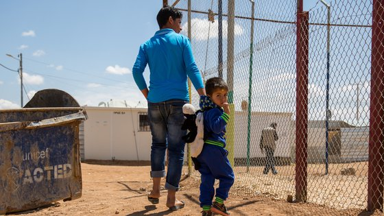 Teenager with little boy walking in refugee camp - War Child - Caregiver Support Intervention