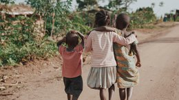 Children in Uganda walking together arm in arm - War Child project