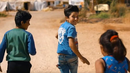 Boys and girl running in refugee camp in Lebanon - War Child