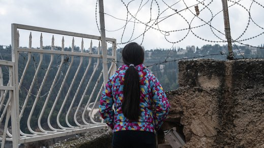 Girl facing away in front of barbed wire in OPT near War Child safe space