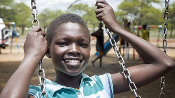 Uganda girl on a swing playing