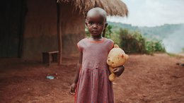 Girl Uganda with teddy bear in hands looking into the camera - War Child projects